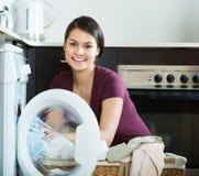 Young woman near washing machine Stock Images