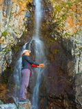 Young woman near waterfall in the mountains, Ala-Archa, Kyrgyzst Royalty Free Stock Image