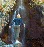Young woman near waterfall in the mountains, Ala-Archa, Kyrgyzst Stock Photography