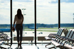 Young woman near window in an airport lounge Royalty Free Stock Photos