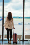 Young woman near window in an airport lounge waiting for arrive Stock Images
