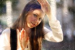 Young woman near the window after the rain Stock Images