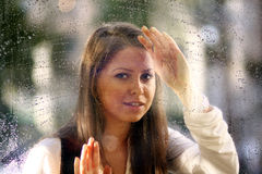 Young woman near the window after the rain Stock Photography
