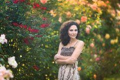 A young woman near yellow roses bush, looking to the left through a shoulder. Royalty Free Stock Photo