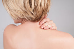 Young woman with neck pain, massaging her shoulder. Young woman with neck pain. Woman holds a hand on neck massaging her shoulder royalty free stock images