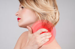 Young woman with neck pain, massaging her shoulder. Young woman with neck pain. Woman holds a hand on neck massaging her shoulder stock photo