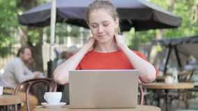 Young Woman with Neck Pain Using Laptop in Cafe Terrace stock video