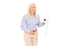 Young woman in need to pee holding a toilet paper Stock Photography