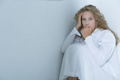 Young woman after nervous breakdown. Sitting in a white hospital room Stock Photo