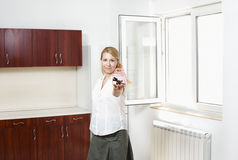 Young woman in new apartment. Concept of young woman with key and symbol of house sitting Royalty Free Stock Photos