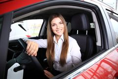 Young woman in new car smiling Stock Photo