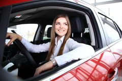 Young woman in new car smiling stock photography