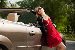 Happy young fashion woman by her convertible car. Happy young fashion blond woman by her convertible car Royalty Free Stock Photos