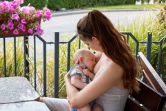 Young woman, new mother breastfeeding and caring her cute baby with love and kindness, nursing newborn outside on daylight royalty free stock photo