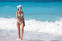 The young woman in the New Year's cap walks on a beach in a sunny day Stock Photo