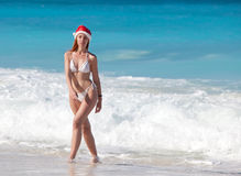 The young woman in the New Year's cap walks on a beach in a sunny day Royalty Free Stock Image