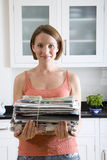 Young woman with newspaper bundle in kitchen, portrait, close-up. Young women with newspaper bundle in kitchen, portrait, close-up Royalty Free Stock Photos