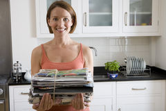 Young woman with newspaper bundle in kitchen, smiling, portrait Royalty Free Stock Images