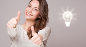 Young woman next to creativity symbol. Royalty Free Stock Photo