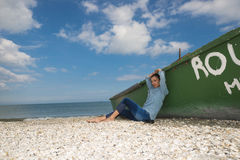 Young woman next to an old boat Royalty Free Stock Images