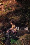 Young woman with a nice dress sitting on a rock in the river stock photos