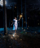 Young woman at night forest with full moon jumping high to reach Royalty Free Stock Photos