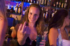 Young woman in nightclub beckoning to camera. Holding drink and smiling royalty free stock photography