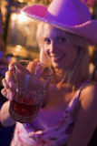 Young woman in nightclub holding drink to camera Royalty Free Stock Photos