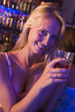 Young woman in nightclub smiling at camera Royalty Free Stock Photos