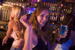 Young woman in nightclub smiling and waving stock photography