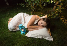 Young woman in nightgown sleeping on grass at garden at night Stock Photo