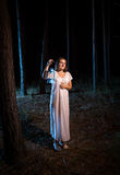 Young woman in nightgown walking in forest at night with gas lam Royalty Free Stock Photos