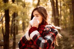 Young woman with nose wiper near autumn tree. Sick girl with runny nose and fever. Showing sick woman sneezing at autumn. Young woman with nose wiper near aun royalty free stock images