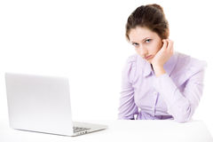 Young woman not in the mood for work in front of laptop. Young woman with sullen look, not in the mood for work, tired, bored, in front of laptop Royalty Free Stock Photography