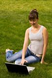 Young woman with notebook. On the grass Royalty Free Stock Image