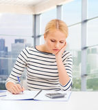 Young woman with notebook and calculator Royalty Free Stock Photography