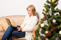 Young woman with a notebook near Christmas tree Stock Photography