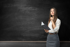Young woman with notebook and pen looking pensively on the background of blackboard Stock Photo