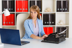Young woman with notebook and typewriter. Royalty Free Stock Photo