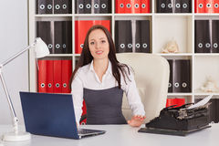 Young woman with notebook and typewriter. Royalty Free Stock Photography