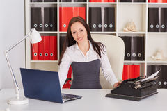 Young woman with notebook and typewriter. Stock Photos