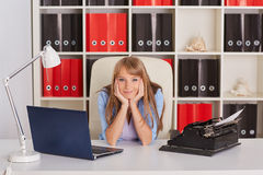 Young woman with notebook and typewriter. Royalty Free Stock Images