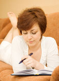Young woman with notepad or organiser writing. At bedroom Royalty Free Stock Images