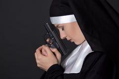 Young woman nun praying with gun over grey Stock Photography