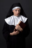 Young woman in nun veil with book over grey Royalty Free Stock Images