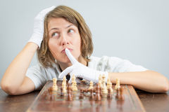 Young woman nurse doctor playing chess checkmate thinking game pieces. Royalty Free Stock Image