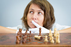 Young woman nurse doctor playing chess checkmate thinking game pieces. Stock Images
