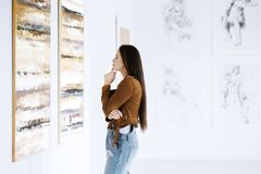 Young woman observing painting Stock Photos