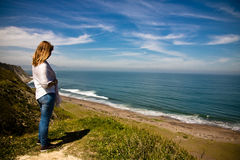 Young woman observing picturesque atlantic coast in springtime Royalty Free Stock Images