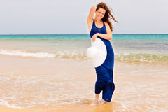 Young woman on the ocean beach. Young woman with white hat walking on a beach Stock Photo